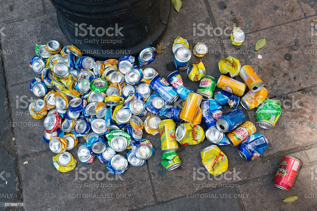 Crushing and recycling aluminum cans on city sidewalk stock photo