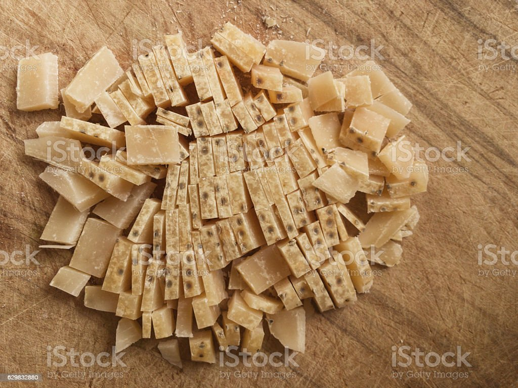 Crust of Parmesan cheese being prepared stock photo