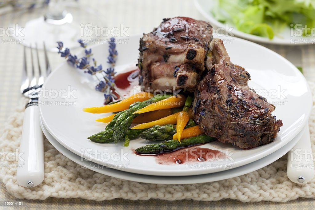 Crusted rack of lamb with lavender and greens stock photo
