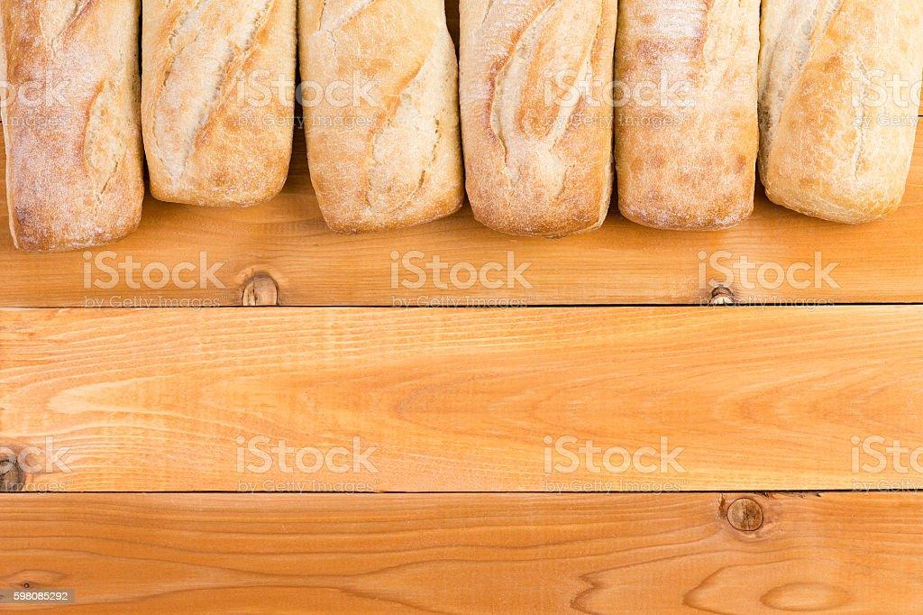 Crusty fresh bread loaf border on wood stock photo