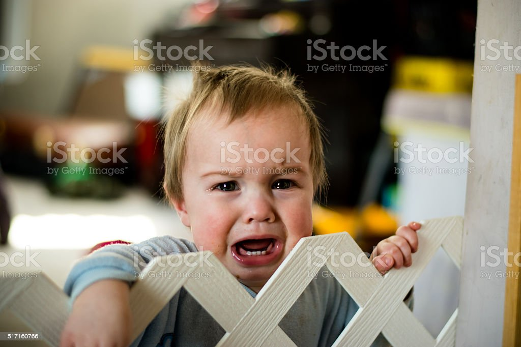 Crying baby behind a gate stock photo