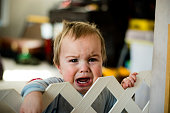 Crying baby behind a gate