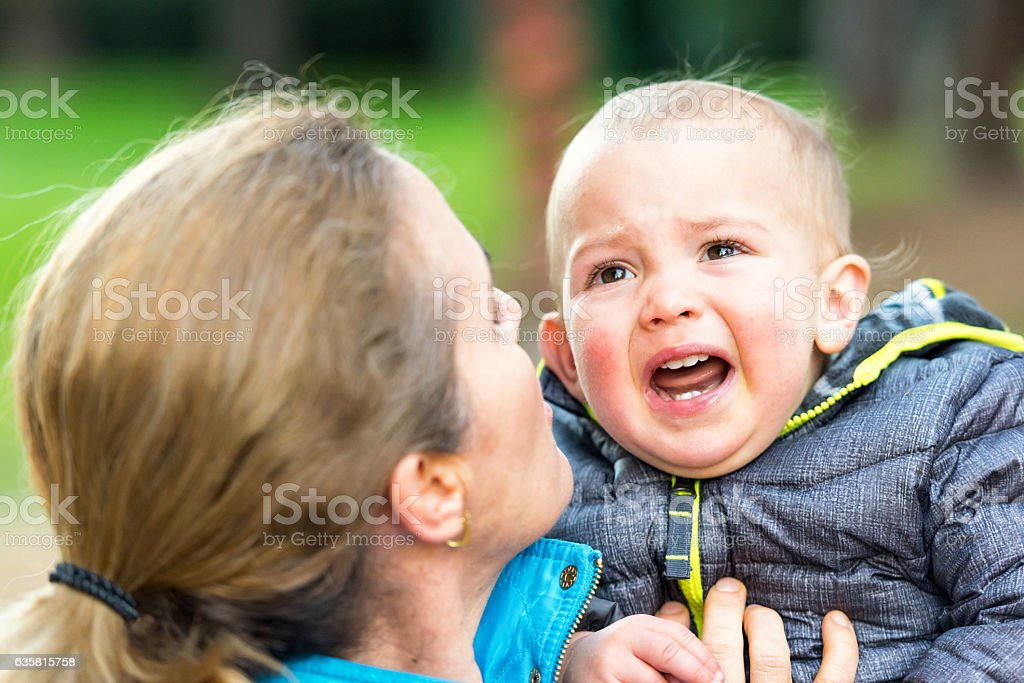 crying baby boy at the park stock photo