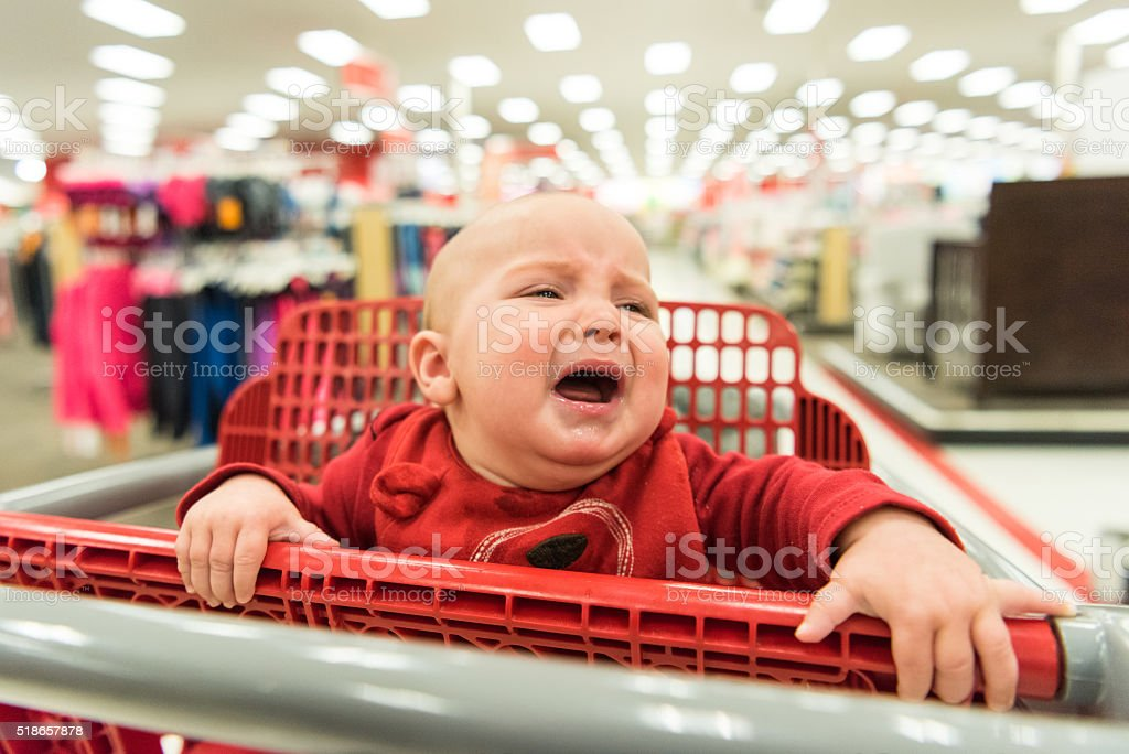 Crying Baby in a shopping cart stock photo