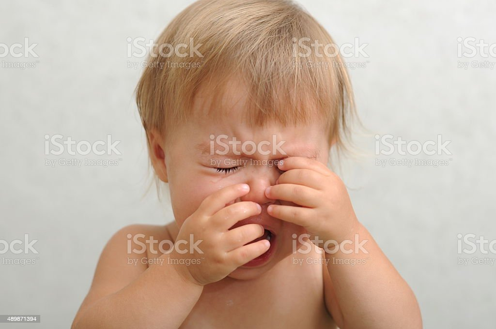 crying baby rubbing her eyes stock photo