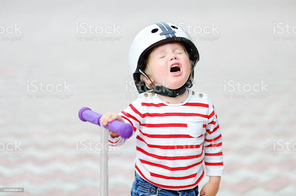 Crying boy in safety helmet with scooter stock photo