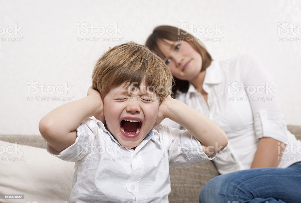 Crying boy is covering his ears stock photo