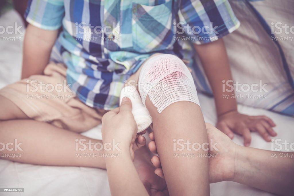 Crying child injured. Mother bandaging son's knee. Vintage tone effect. stock photo