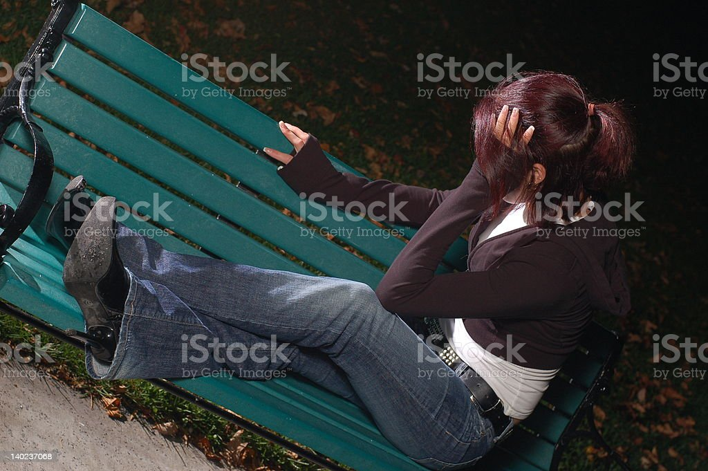 Crying girl on a park bench 3 stock photo