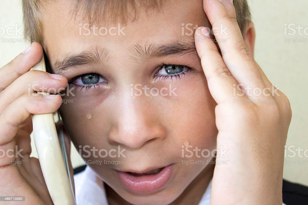 Crying little boy talking on phone in pain stock photo