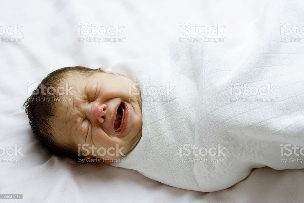 Crying newborn infant in white blanket royalty-free stock photo