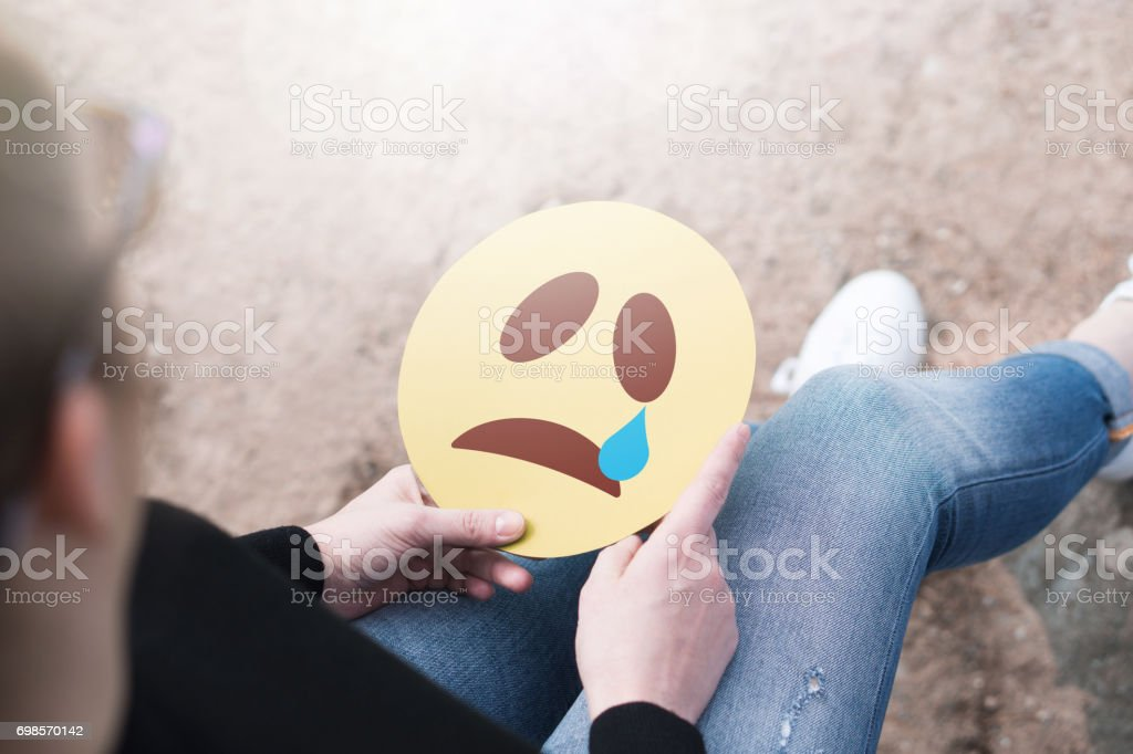 Crying paper emoticon in hand. Depressed woman holding printed sad smiley face and sitting on a rock. Modern   communication and smiley icon on cardboard. Sadness, depression and emotions concept. stock photo