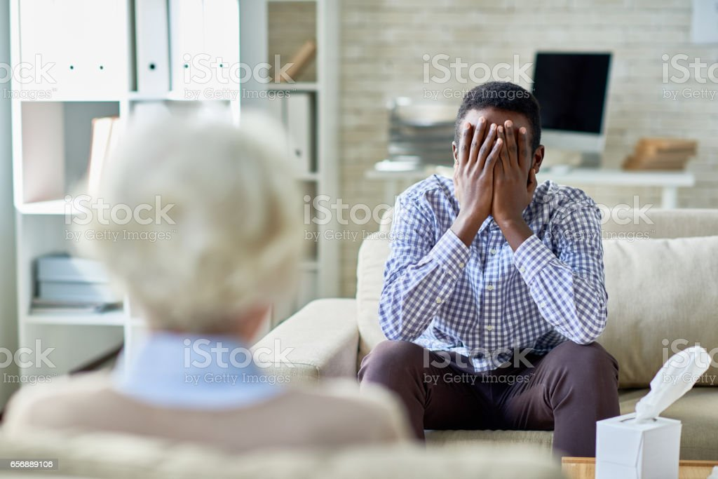 Crying patient at psychologist stock photo