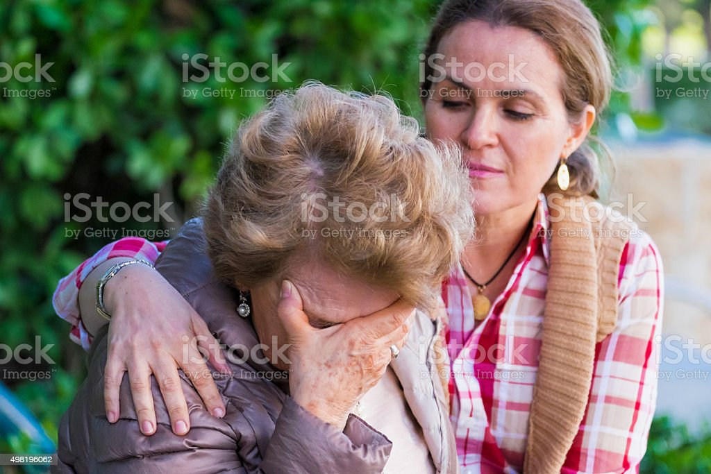 Crying senior woman holding her face being comforted stock photo