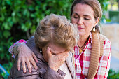 Crying senior woman holding her face being comforted