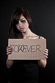 Crying teenage girl holding over sign
