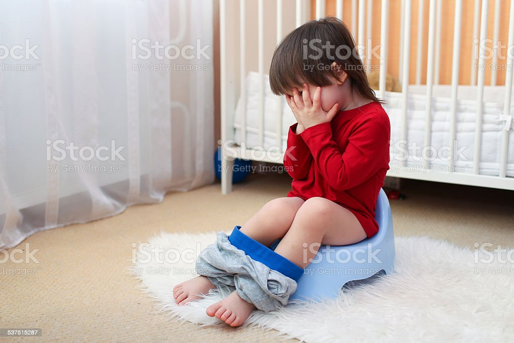 crying toddler sitting on potty at home stock photo