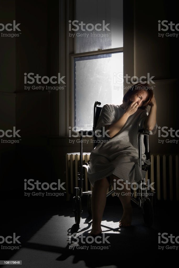 Crying Woman Sitting in Wheelchair by Window, Low Key royalty-free stock photo