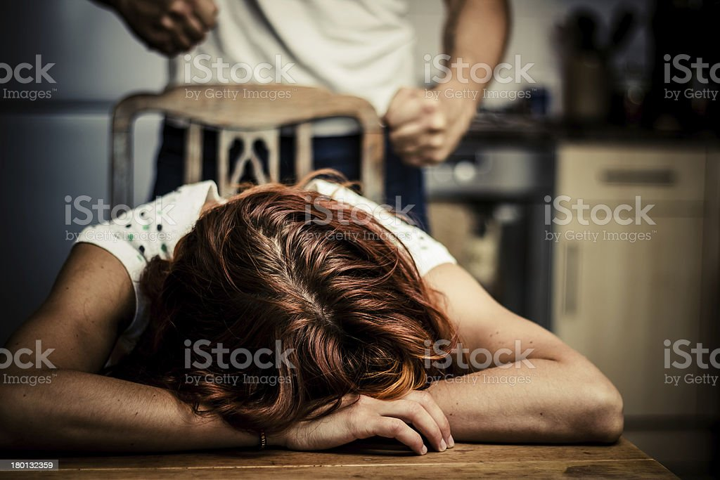 Crying woman with abusive partner behind her stock photo