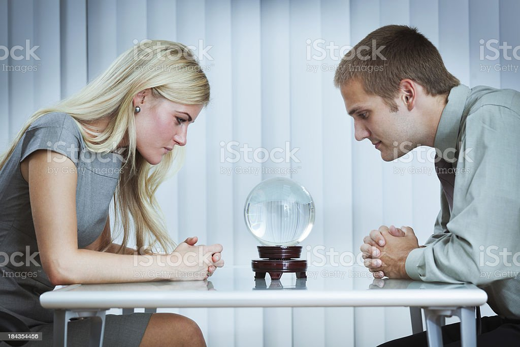 Business Persons Looking into Crystal Ball for Outlook on Future stock photo