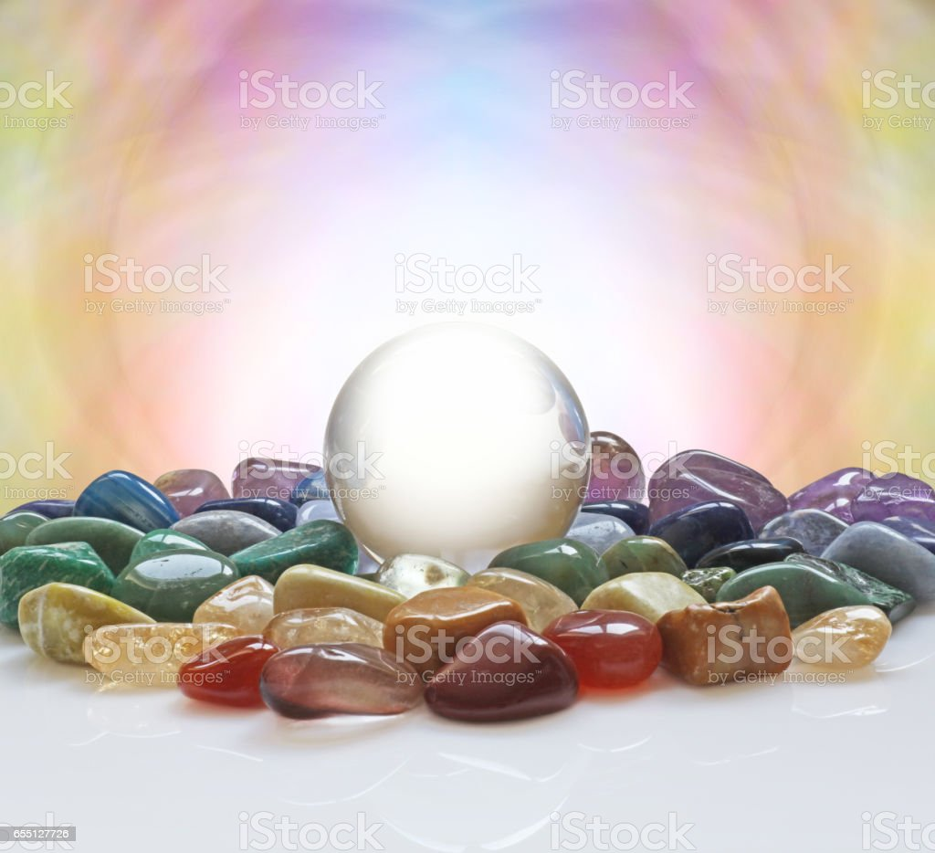 Crystal ball surrounded by healing crystals stock photo