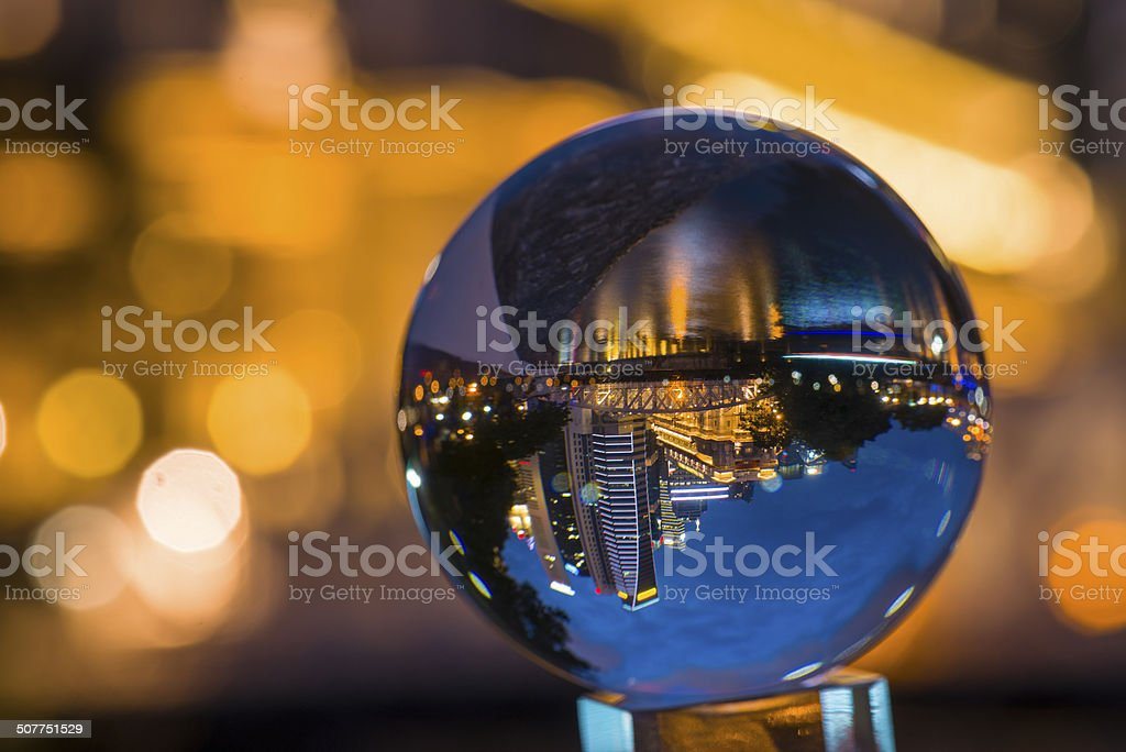 Crystal ball with reflection of city night scene. stock photo