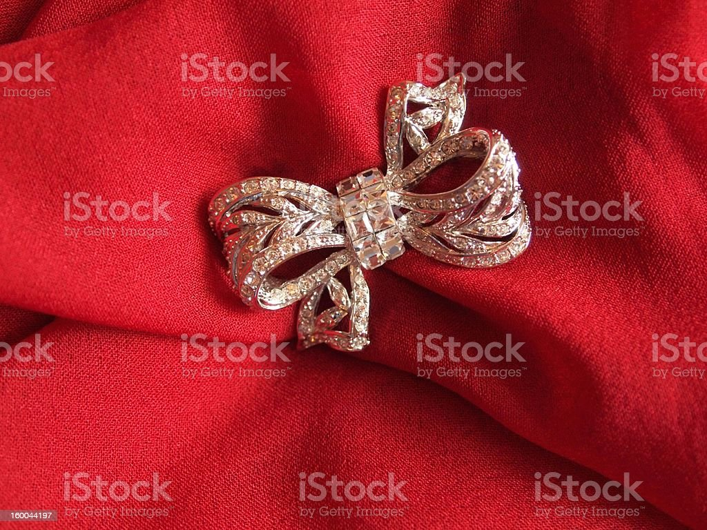 Crystal bow brooch on red scarf royalty-free stock photo