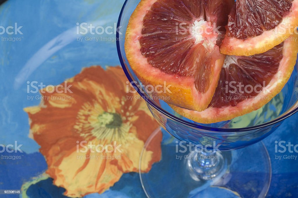 Crystal bowl of blood oranges on a blue poppy plate royalty-free stock photo