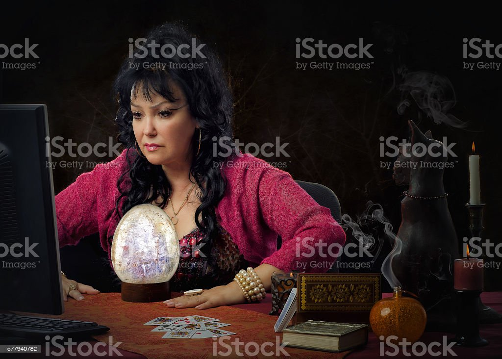 Crystal gazer works online in front of monitor stock photo