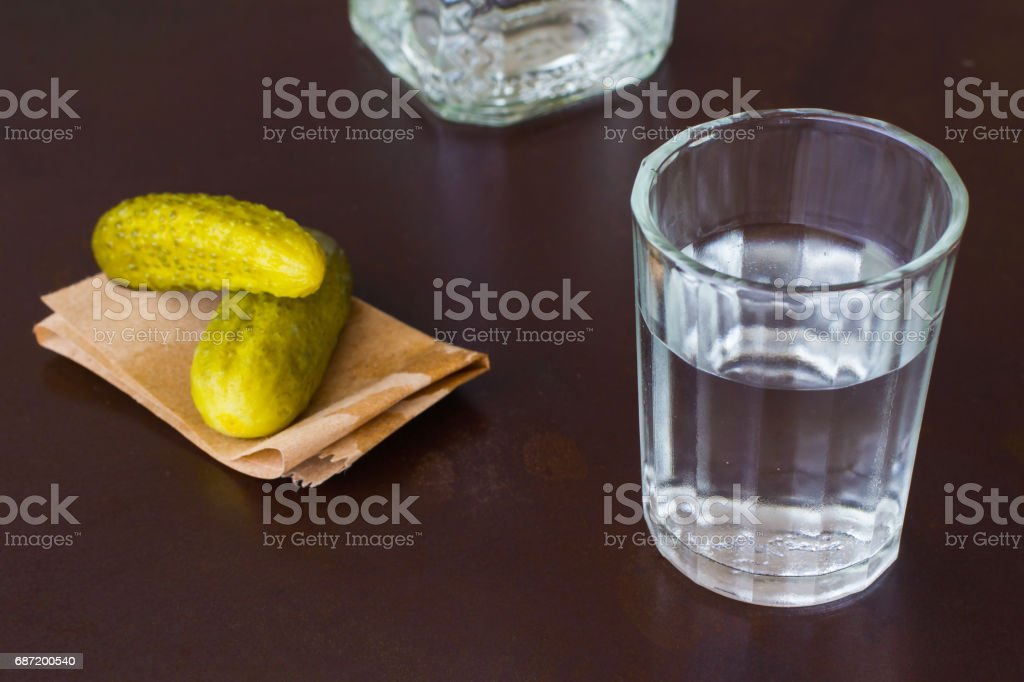 Crystal glass,  bottle and pickled cucumber on a dark background stock photo
