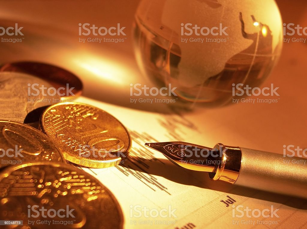 Crystal globe, coins and fountain pen on the stock page royalty-free stock photo