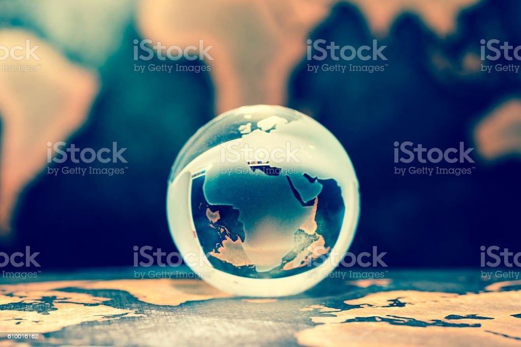 Crystal globe on books against grunge world map stock photo