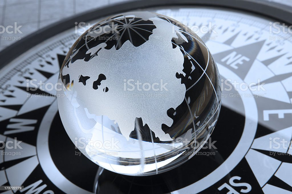 Crystal globe rotated towards Asia on top of compass stock photo