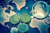 Crystal globe with pile of coins on grunge world map