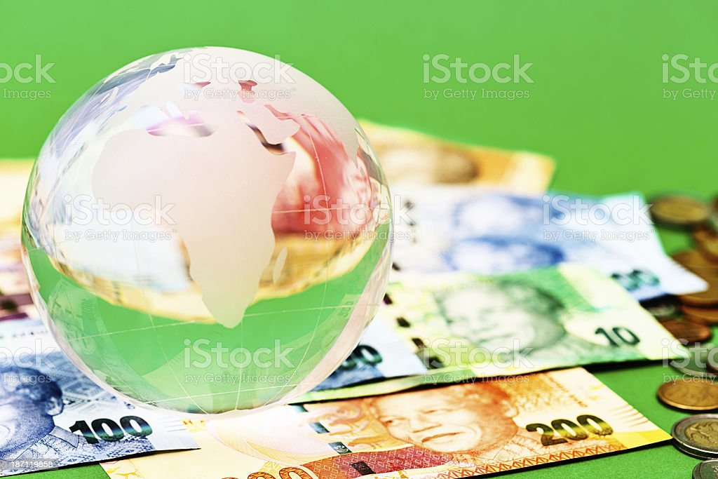 Crystal world-globe paperweight holds down South African money royalty-free stock photo