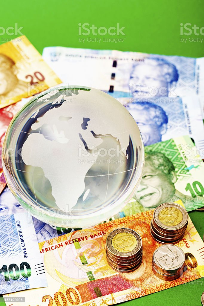Crystal world-globe paperweight resting on South Afrcan currency royalty-free stock photo