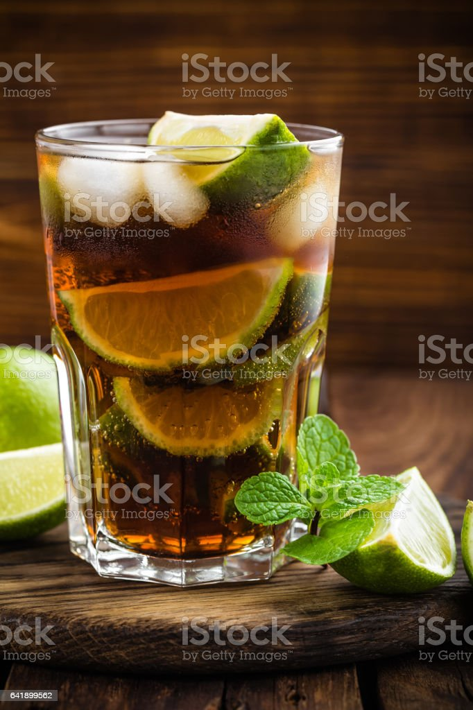 Cuba Libre cocktail with cola, lime and ice in glass stock photo