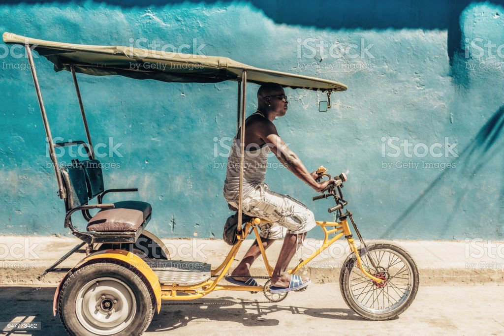 cuban bike-taxi driver on bycicle in front of blue wall stock photo