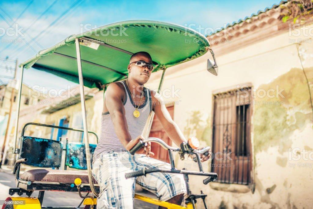 cuban bike-taxi driver with sun glasses in Santiago de Cuba stock photo