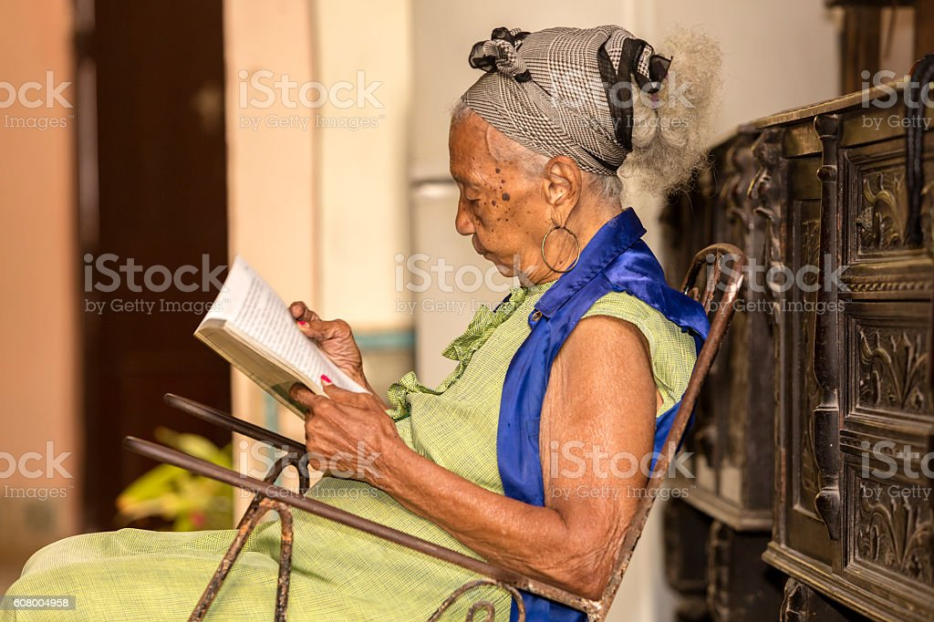 Cuban elderly woman reading a book stock photo