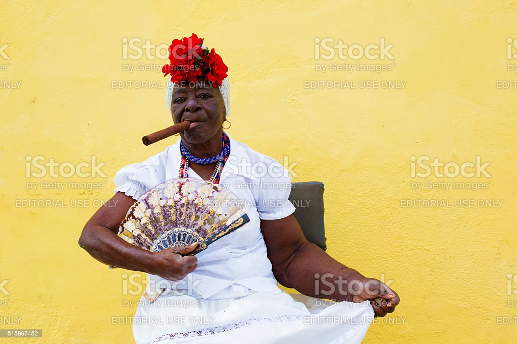 Cuban lady with cigar and fan stock photo