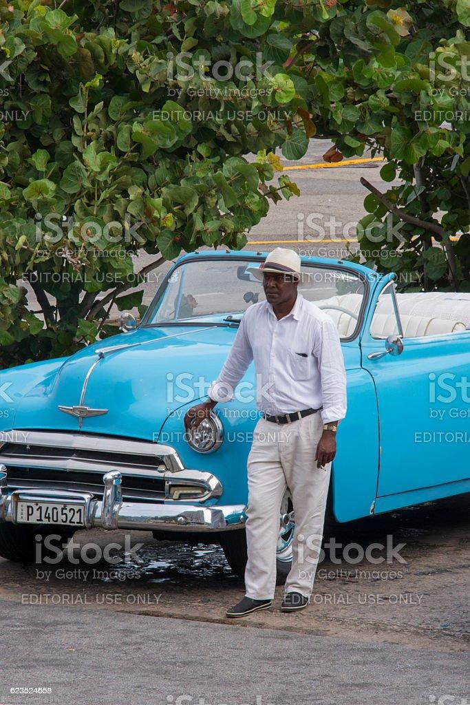 Cuban man next to blue vintage taxi stock photo
