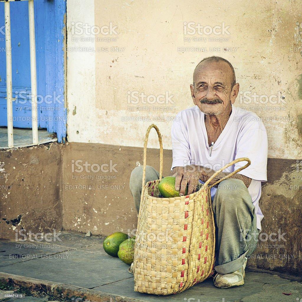 Cuban man selling avocado at a street of Trinidad royalty-free stock photo
