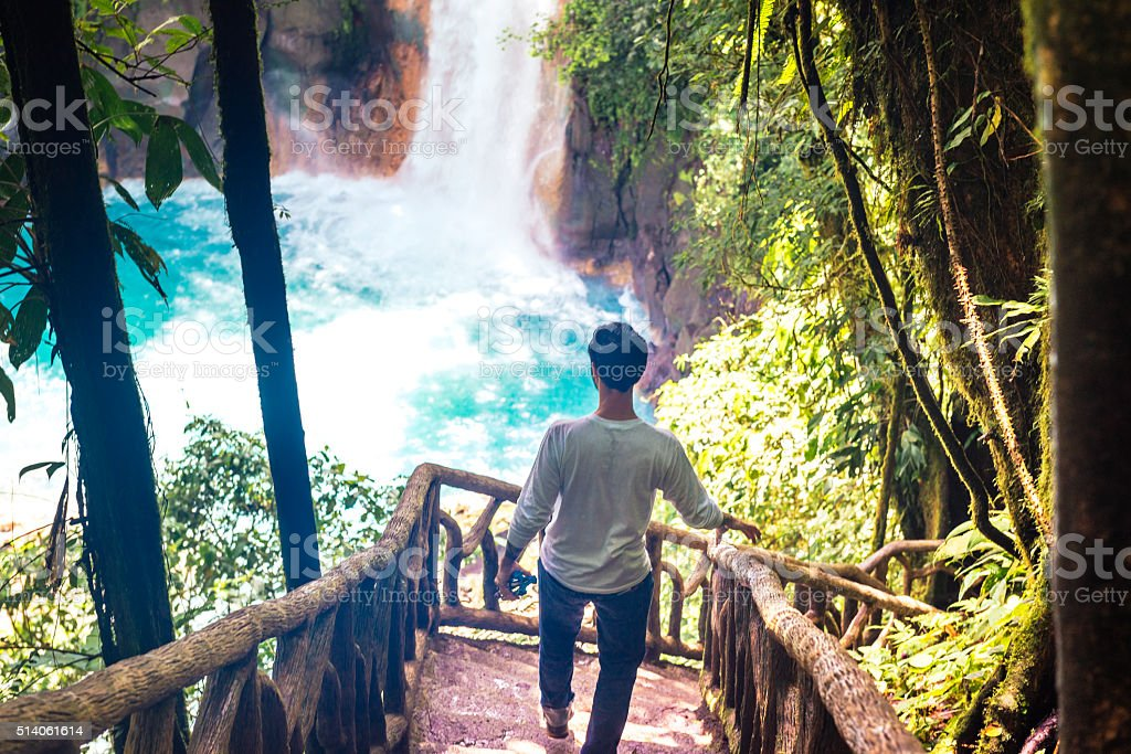 Cuban Man Traveling in Costa Rica Hikes Waterfall Rio Celeste stock photo