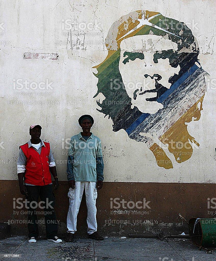 Cuban men next to a mural of Che Guevara stock photo
