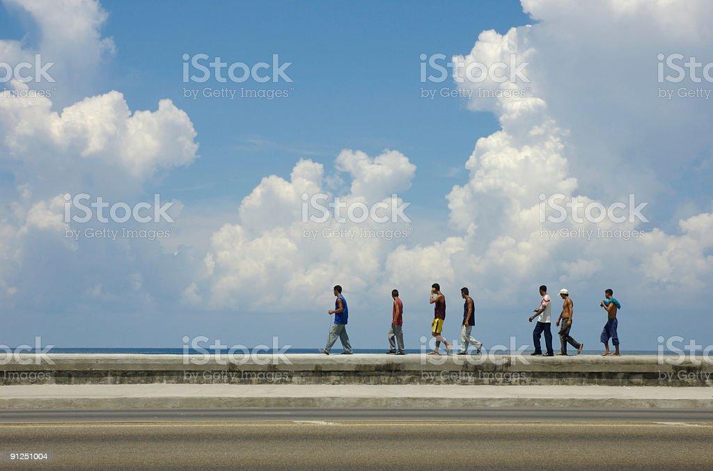 Cuban Men Walk Along the Malecon Sea Wall Havana Cuba royalty-free stock photo