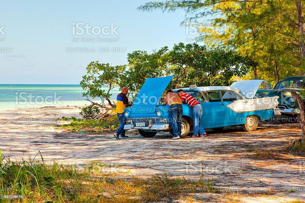 Cubans repair an old classic American vintage car stock photo