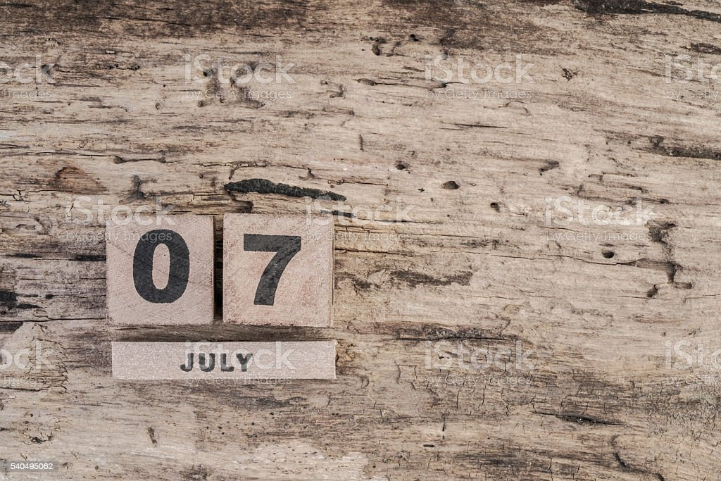 cube calendar for july on wooden background with copy space stock photo