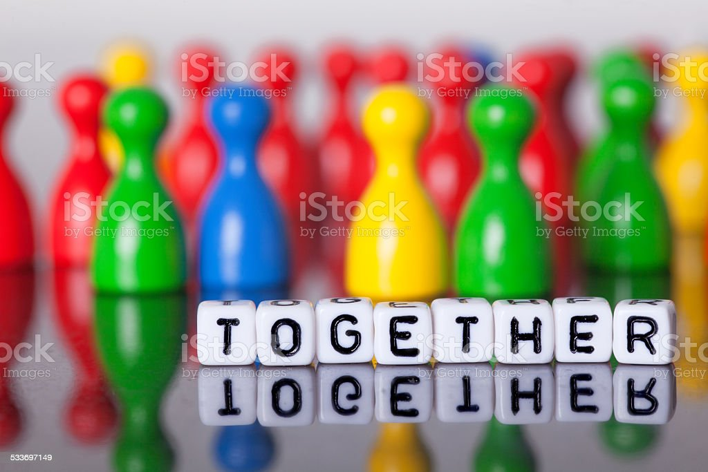 Cube Letters show together  in front of unsharp ludo figures stock photo