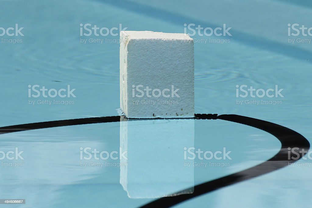 Cube of expanded polystyrene floating in a swimming pool stock photo